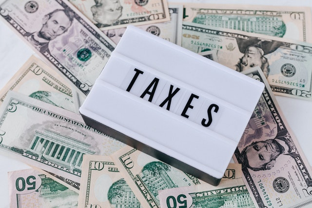 """Heap of U.S. cash topped by a vintage light box that says """"taxes."""""""
